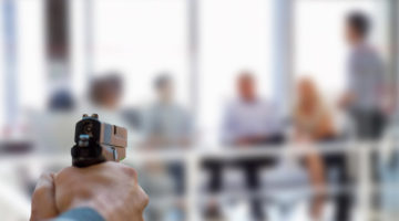 Active shooter aiming gun at business people in a meeting